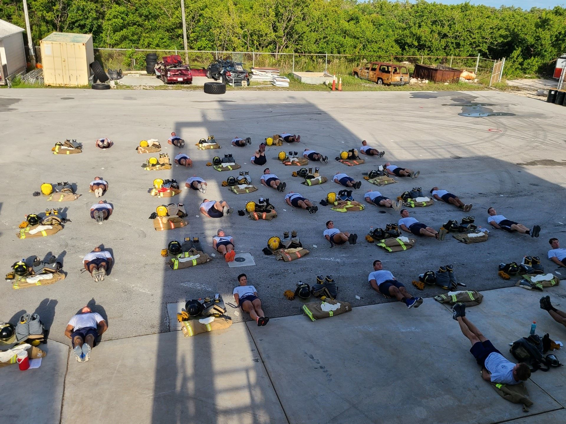 The Hot Shots lay down on the ground and do warm-ups in rows during training.