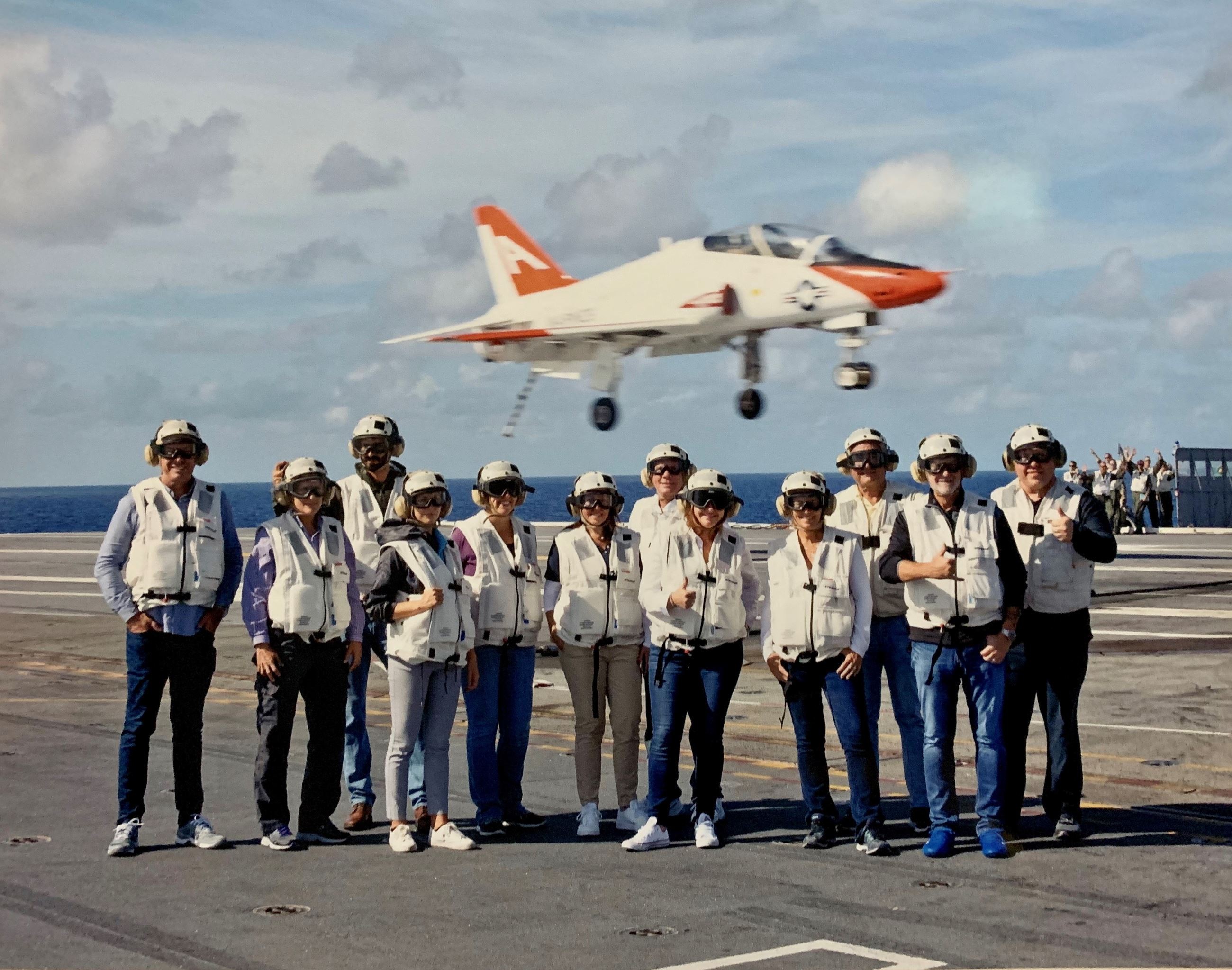 Group picture on the deck of the USS Stennis with airplane landing onboard