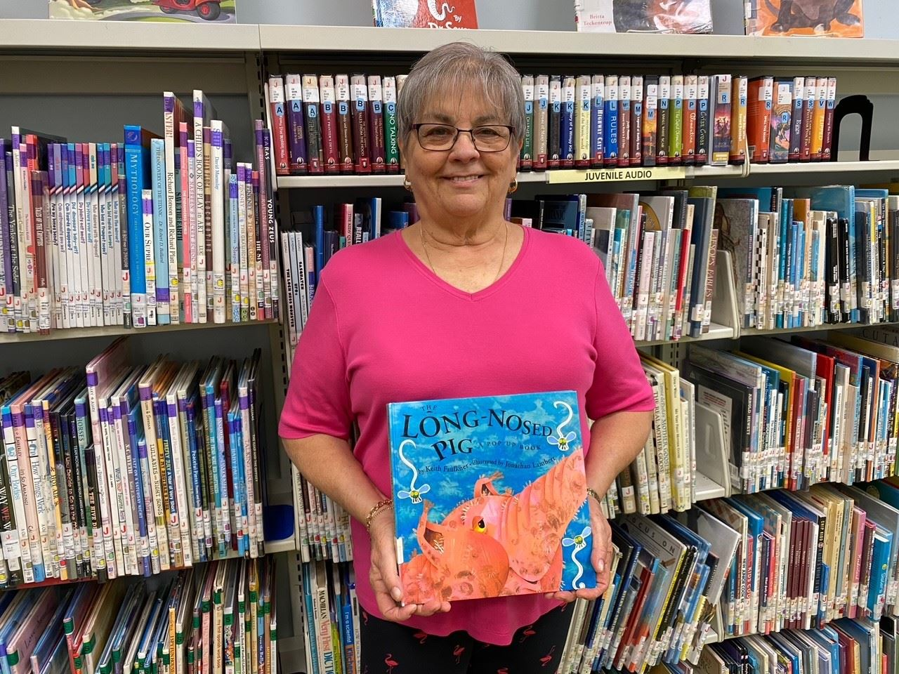 Teresa Valdez holds up her favorite book in front of a bookcase